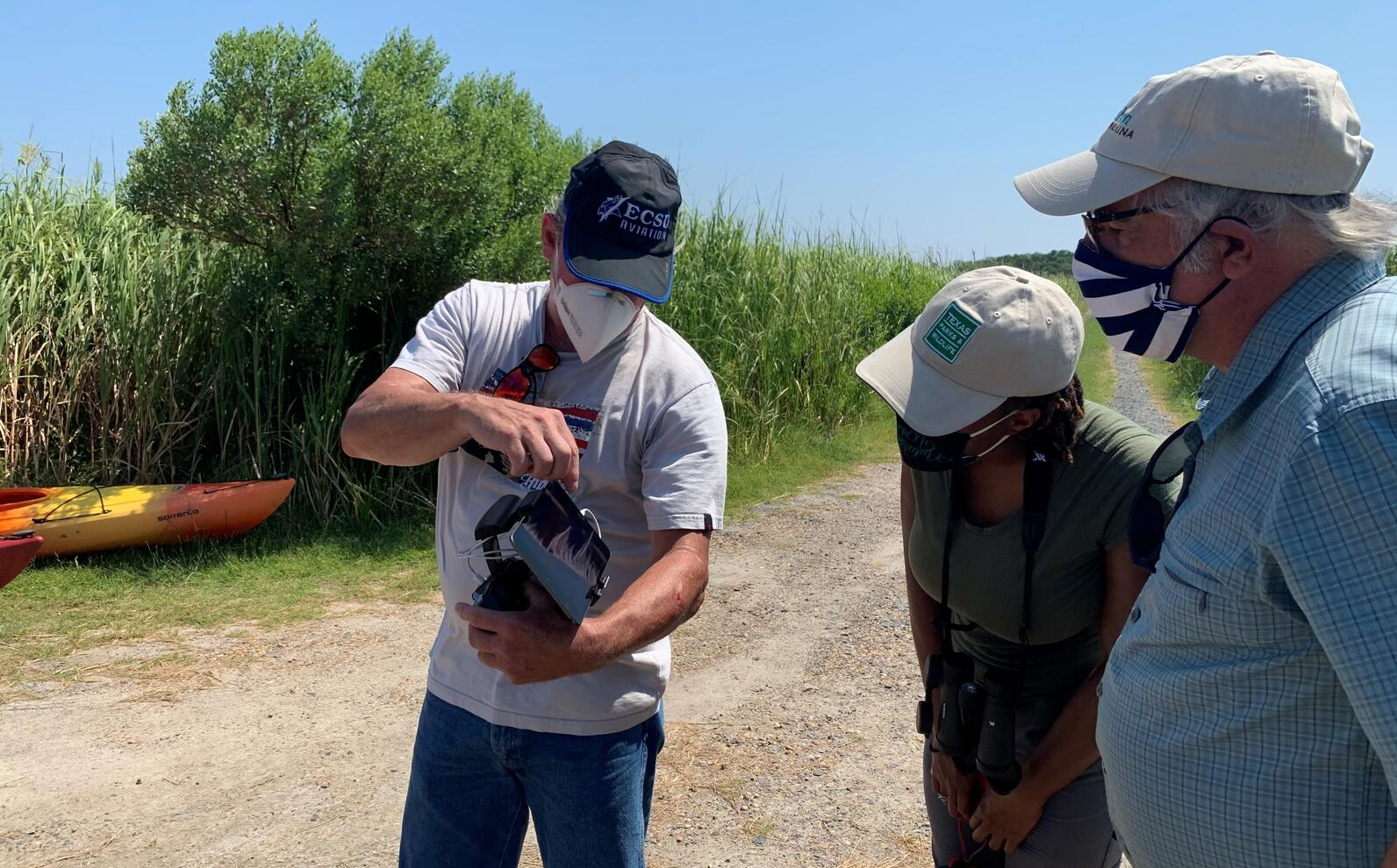 ECSU drone pilot Aron Bechiom shows Audubon staff the drone view of the sanctuary marsh.